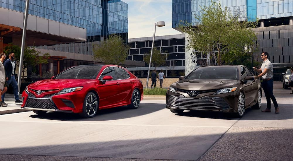 A red 2020 Toyota Camry is parked next to a grey Camry in front of glass buildings.