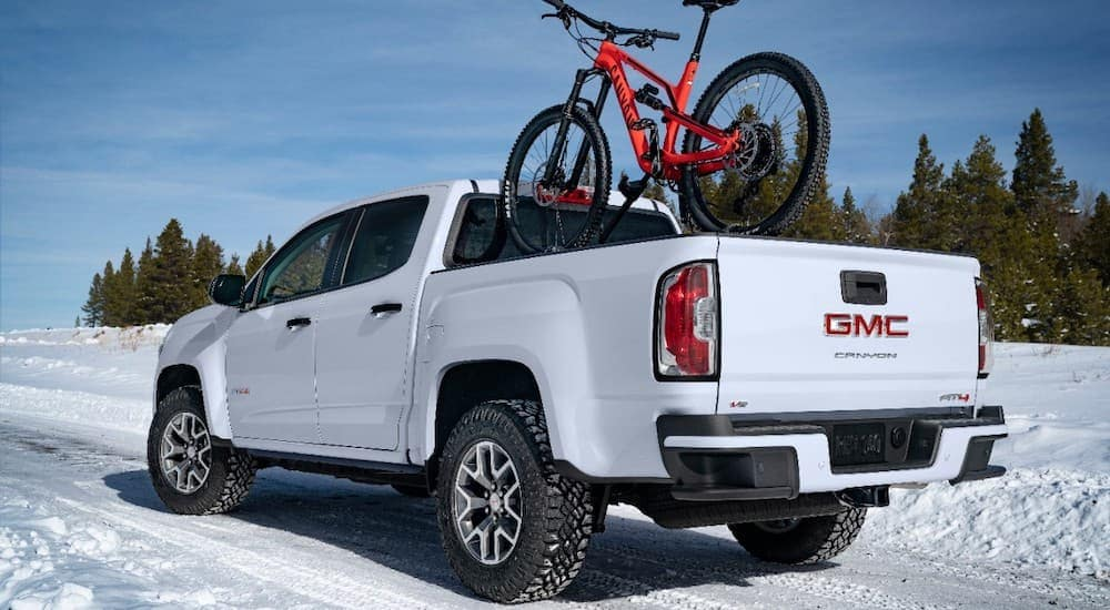A white 2021 GMC Canyon AT4 is in the snow with a red bike in the bed.
