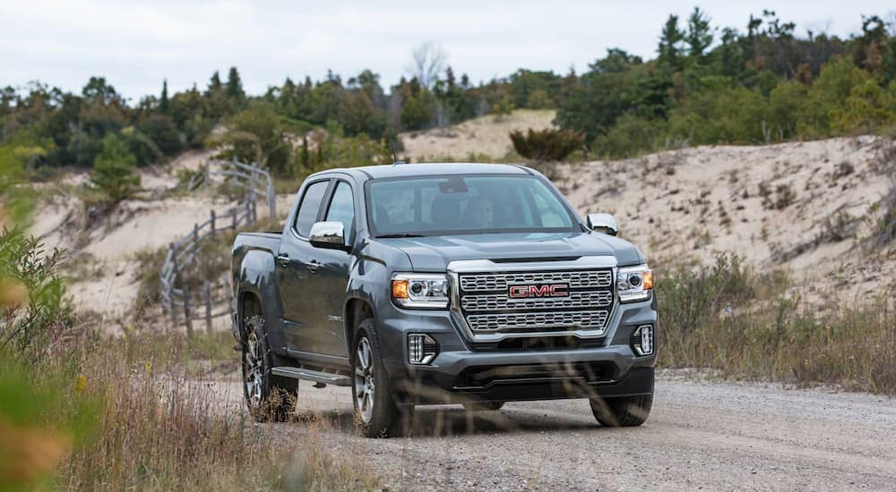 A grey 2021 GMC Canyon is driving on a dirt road.