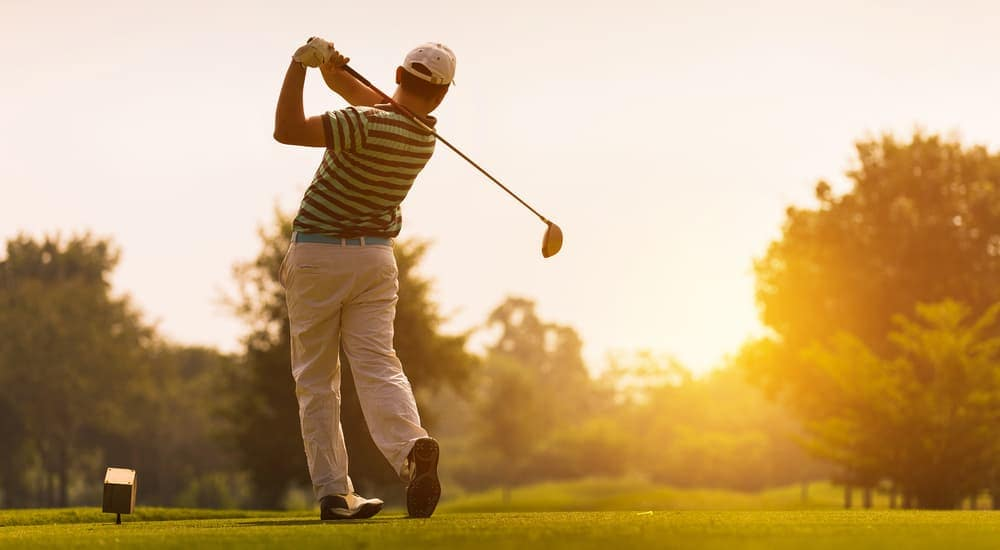 A man is in mid swing at a golf course at dusk.