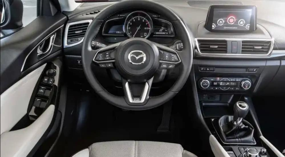 The front black and grey leather interior of a used Mazda 3 is shown.