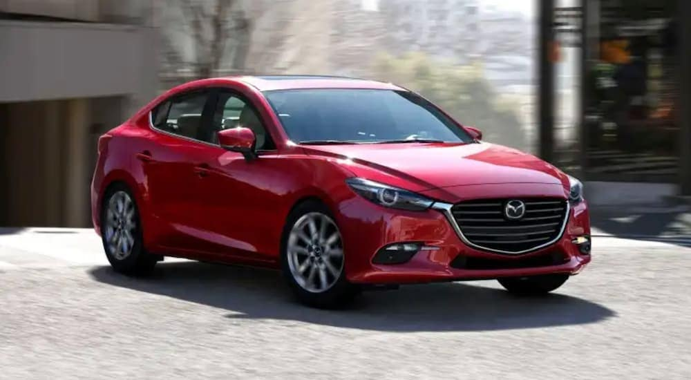 A red 2018 used Mazda 3 is driving around a corner near Indiana, PA.