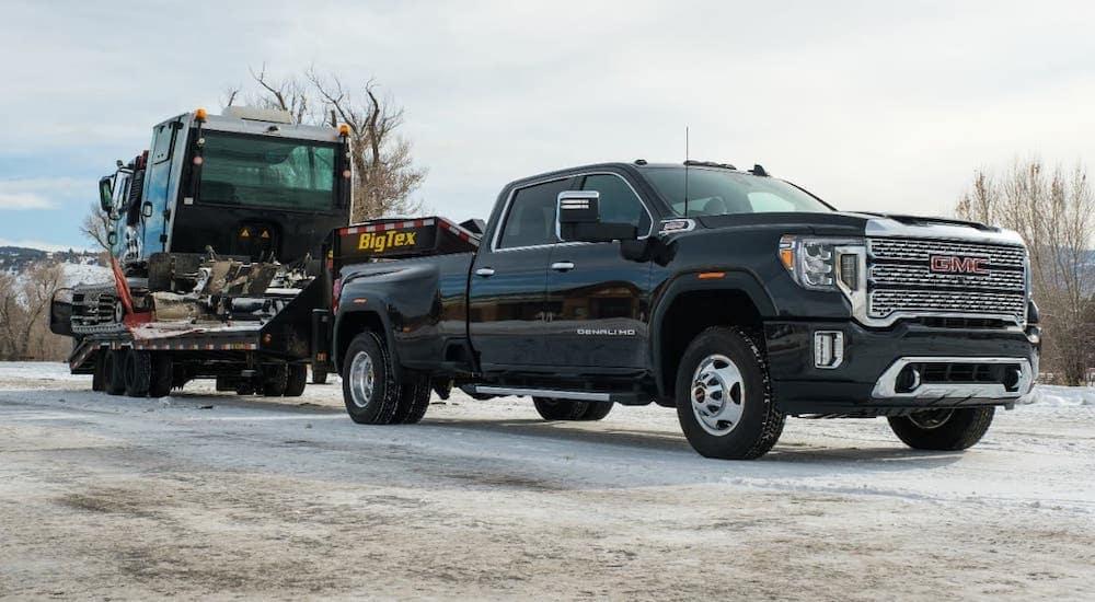 A black 2020 GMC Sierra HD Denali is towing a trailer and heavy snow equipment.