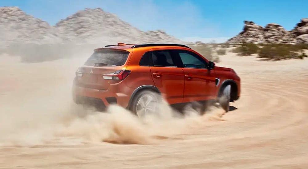 An orange 2020 Mitsubishi Outlander Sport is kicking up dirt in a desert.