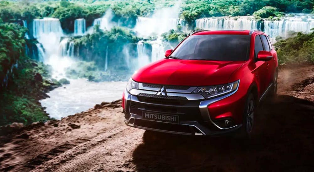 A red 2020 Mitsubishi Outlander is parked in front of waterfalls on a dirt trail.
