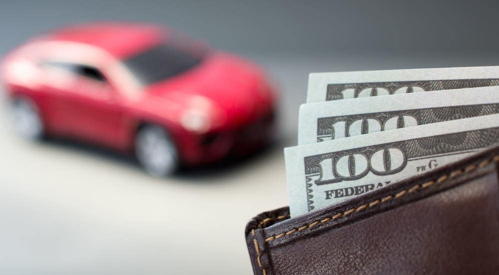 A closeup of a wallet with hundred dollar bills is in front of a red car found at Used Car Dealership Near Me.
