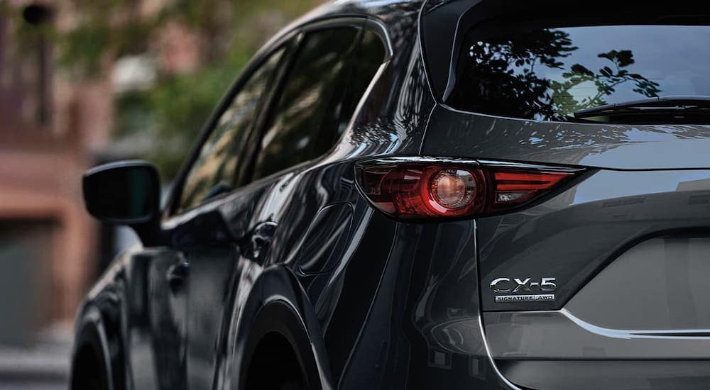 A gray 2020 Mazda CX-5 is shown from the rear. See one at your local Mazda dealer.