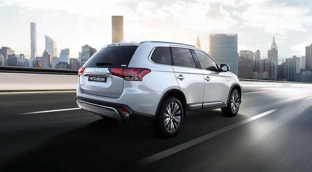 A white 2020 Mitsubishi Outlander is driving towards a city.