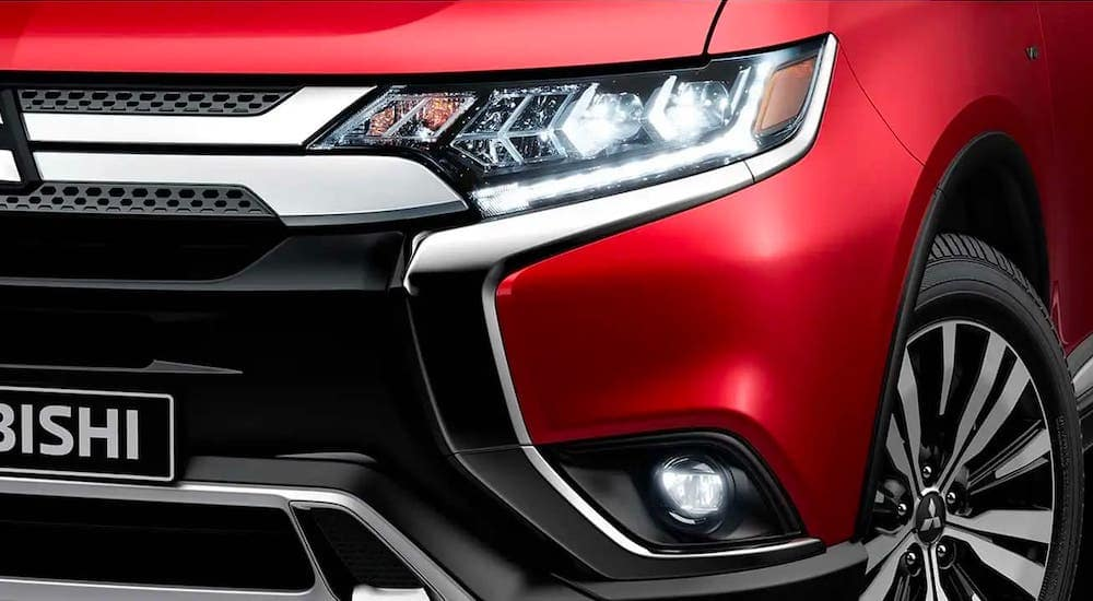 A closeup of a headlight is shown on a red 2020 Mitsubishi Outlander. Ask your Indiana, PA Mitsubishi Dealer about the 2021 model.