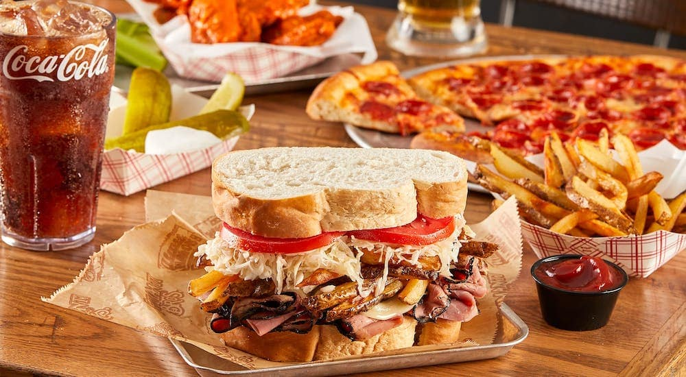 The Almost Famous sandwich from Primanti Bros is shown in front of Pizza, Wings and a soda.