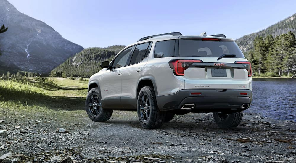 A white 2020 GMC Acadia AT4 is parked on gravel next to a lake and mountains.