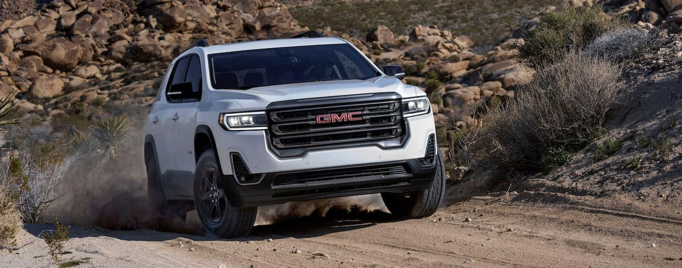 A white 2020 GMC Acadia AT4 is off-roading on a dirt trail.