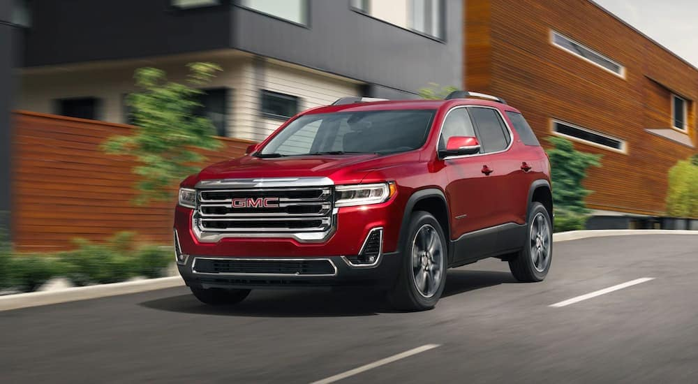 A red 2020 GMC Acadia, which is popular among GMC SUVs, is driving past grey and brown condos.