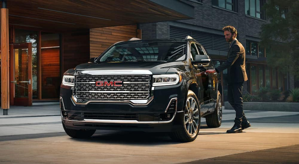 A man is getting in his black 2020 GMC Acadia, popular among GMC SUVs in Indiana, PA, at a modern building at night.