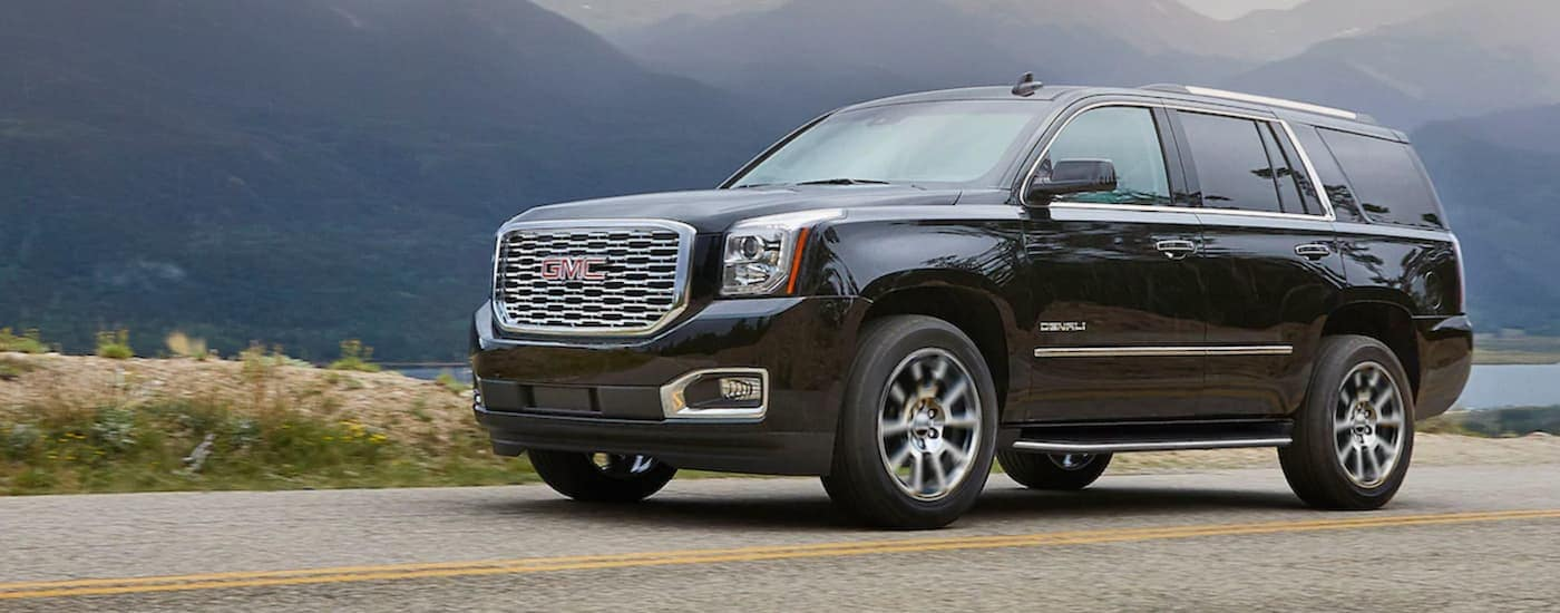 A black 2020 GMC Yukon is driving past a lake and mountains.