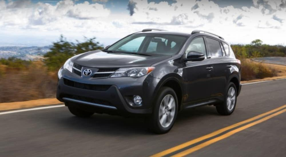A dark grey 2013 Toyota RAV4 is driving on a winding road with hills in the distance.