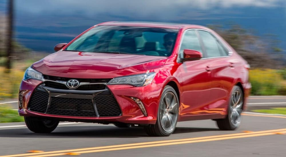 A red 2015 Toyota Camry is driving on a winding road after leaving a used car dealership near me.