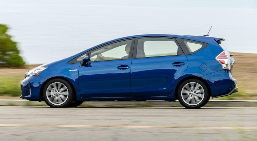 A blue 2016 Toyota Prius is shown driving from the side.