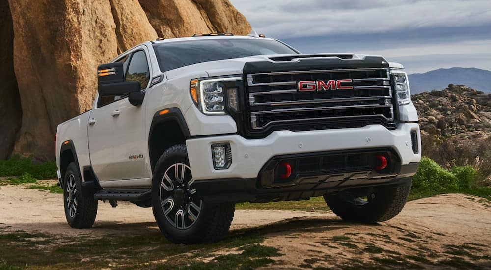 A white 2020 GMC Sierra 2500 is parked in front of a large desert rock.