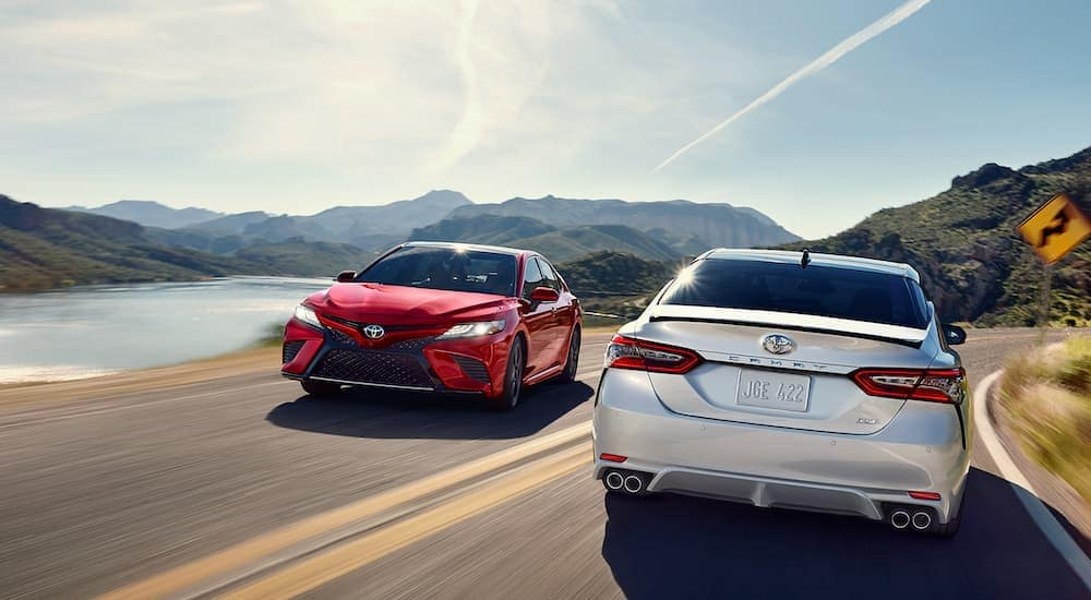 A white 2019 Toyota Camry, which is popular among used cars, is driving past a red one on a road next to a lake.
