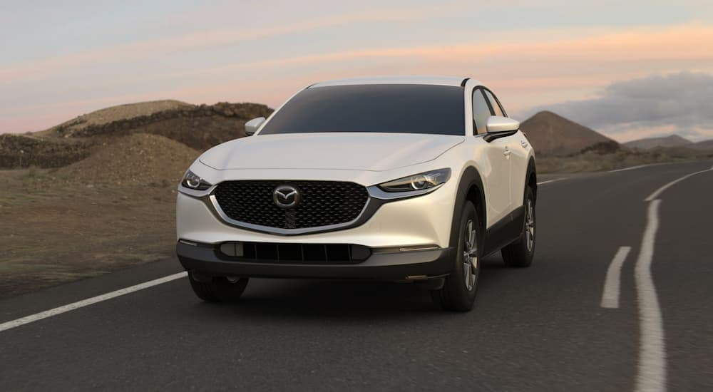 A white 2021 Mazda CX-30 is driving at sunset past hills after leaving a Mazda dealer near me in Indiana, PA.