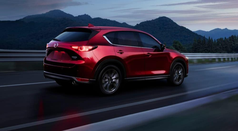 A red 2021 Mazda CX-5 is driving on a dark road toward mountains.