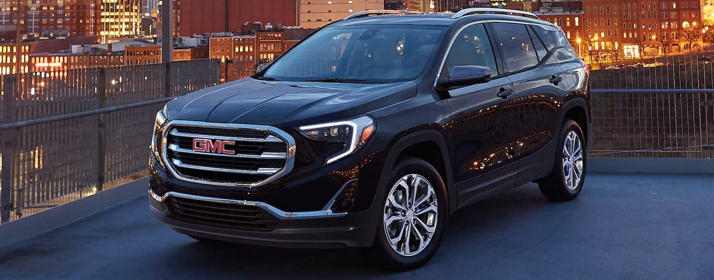 A black 2020 GMC Terrain from a GMC dealer is parked on a city rooftop parking area.