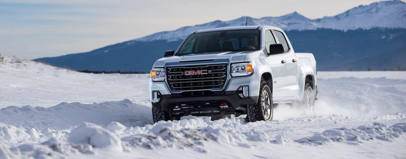 A white 2021 GMC Canyon AT4 from a local GMC dealer is driving through snow.