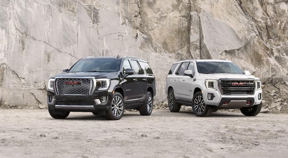 A black 2021 GMC Yukon Denali and a white Yukon AT4 are parked in front of a rock face near Indiana, PA.