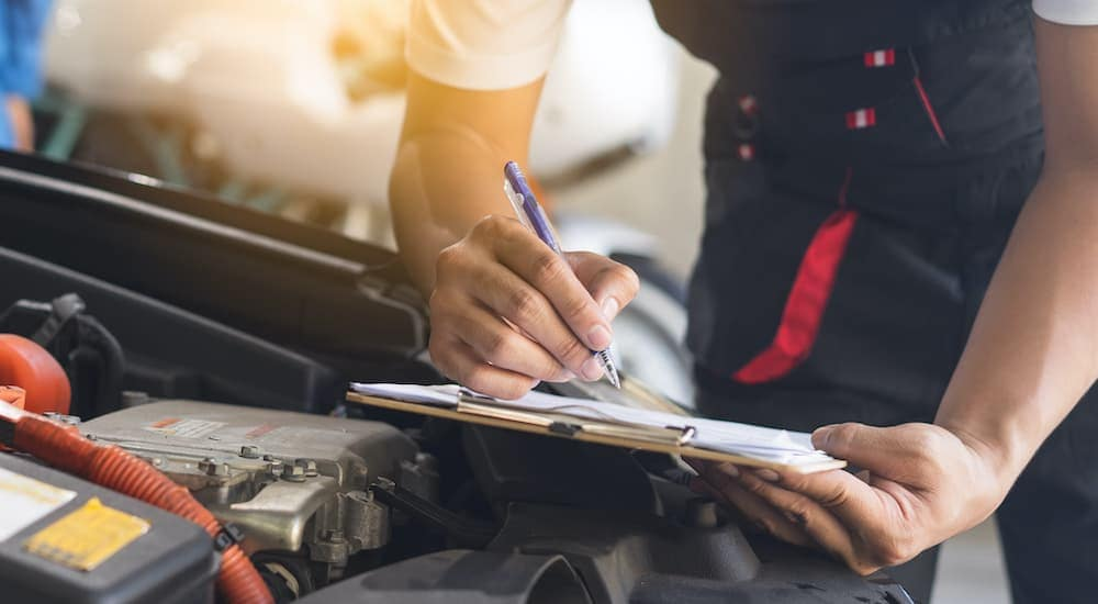 A mechanic is filling out paperwork on a clipboard over an engine bay.