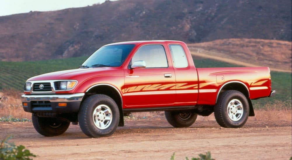 A red 1995 used Toyota Tacoma is shown in a profile view parked on a dirt path.