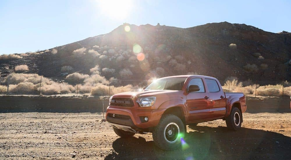 A red 2014 used Toyota Tacoma TRD is parked in the desert.