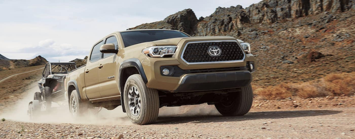 A tan 2019 Used Toyota Tacoma is towing a side by side on a dirt road in the desert.