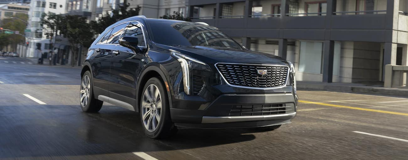 A black 2021 Cadillac XT4 is driving on a city street.