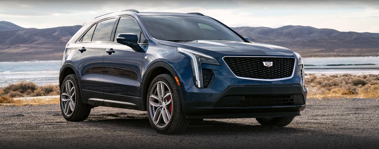 A dark blue 2021 Cadillac XT4 is parked in front of a body of water.