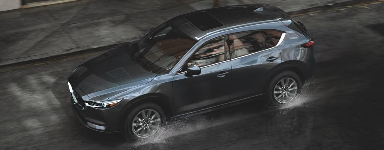 A dark grey 2021 Mazda CX-5 is driving on a wet city street.