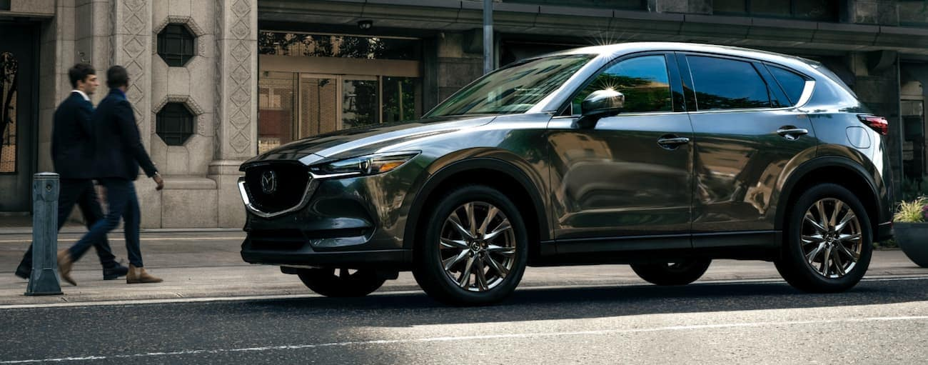A grey 2021 Mazda CX-5 is parked on a city street.