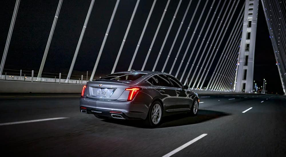 A grey 2020 Cadillac CT5-V is driving over a bridge after leaving the Cadillac dealer.