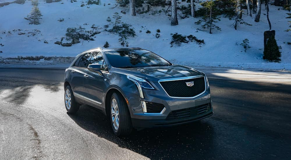 A grey 2021 Cadillac XT5 is driving around a corner with a snowy hill in the background.