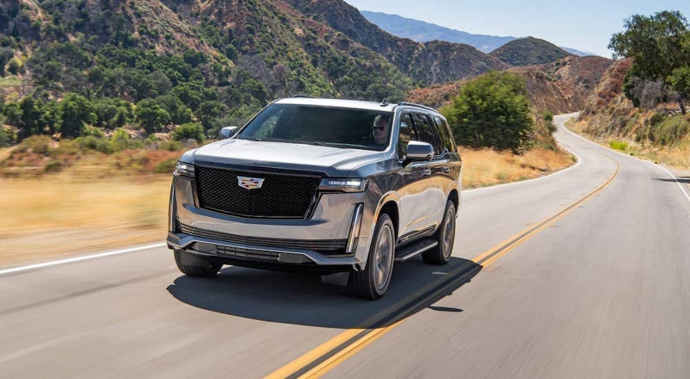 A gray 2021 Cadillac Escalade is shown from the front driving on a mountain highway.