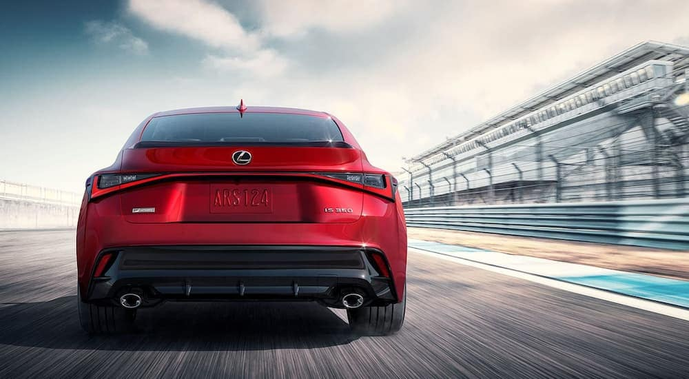 A red 2021 Lexus IS 350 is shown from behind speeding past bleachers at the racetrack.