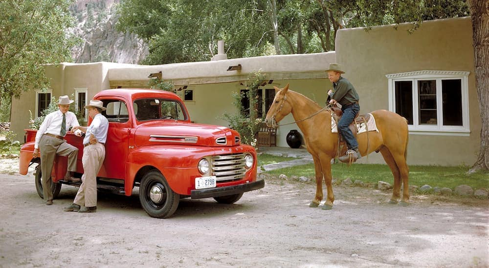 A red 1948 Ford F-1 is shown with two men leaning against it and a man on horseback next to it.