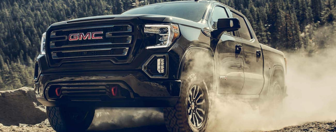 A black 2021 GMC Sierra 1500 is driving on a dirt road.