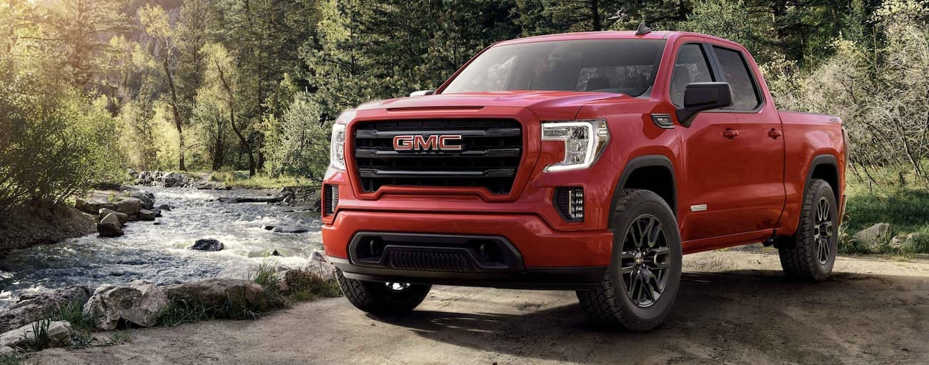 A red 2021 GMC Sierra 1500 is parked next to a river in the woods.