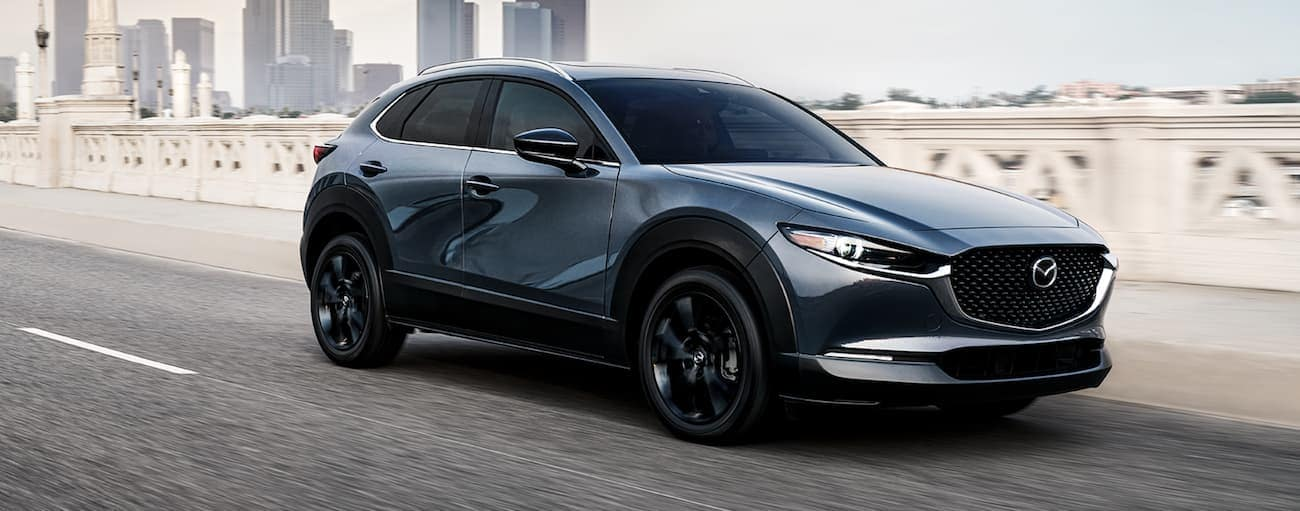 A grey 2021 Mazda CX-30 is driving on a bridge away from a city.