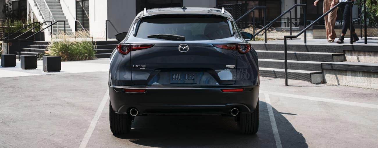 A grey 2021 Mazda CX-30 is shown from the rear in a parking lot.