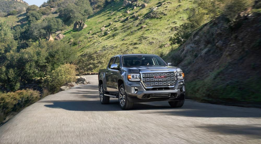 A grey 2021 GMC Canyon Denali is driving on a rural road after leaving a GMC truck dealer near me.