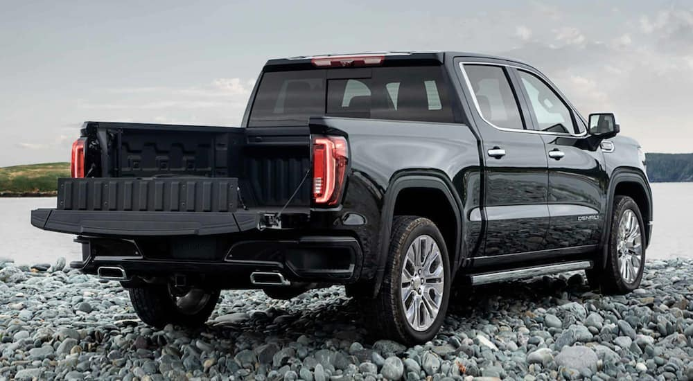 A black 2021 GMC Sierra 1500 Denali with the MultiPro Tailgate is parked on a rocky lake shore.