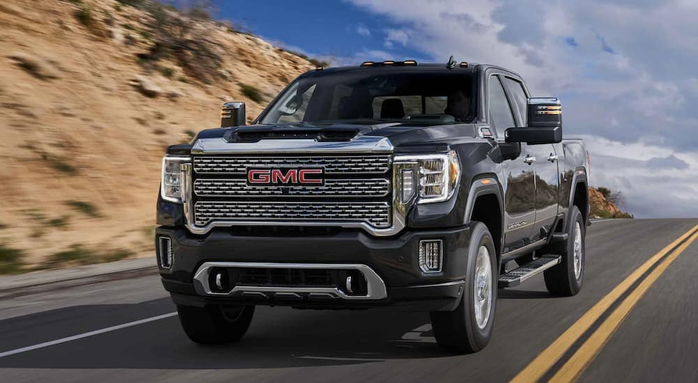 A black 2021 GMC Sierra 2500 Denali is driving on a desert road past a hill.
