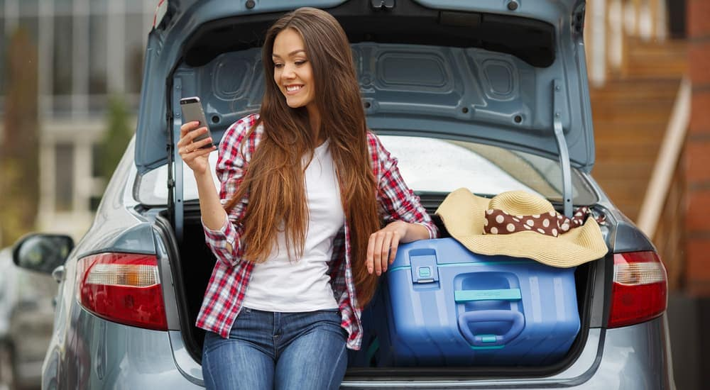 A girl is leaning against an open car trunk with bags.